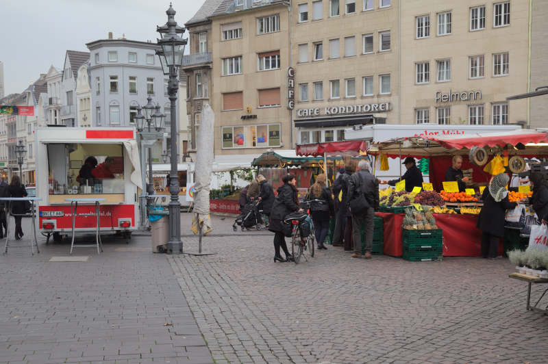 People looking at the fruit not the bratwurst stall